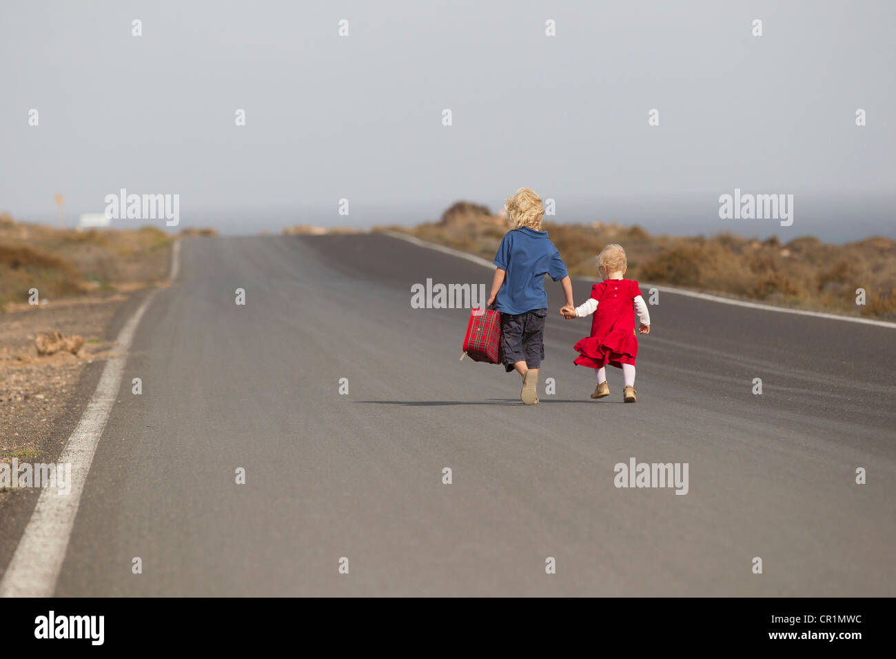 Geschwister, die zusammen auf Landstraße gehen Stockbild