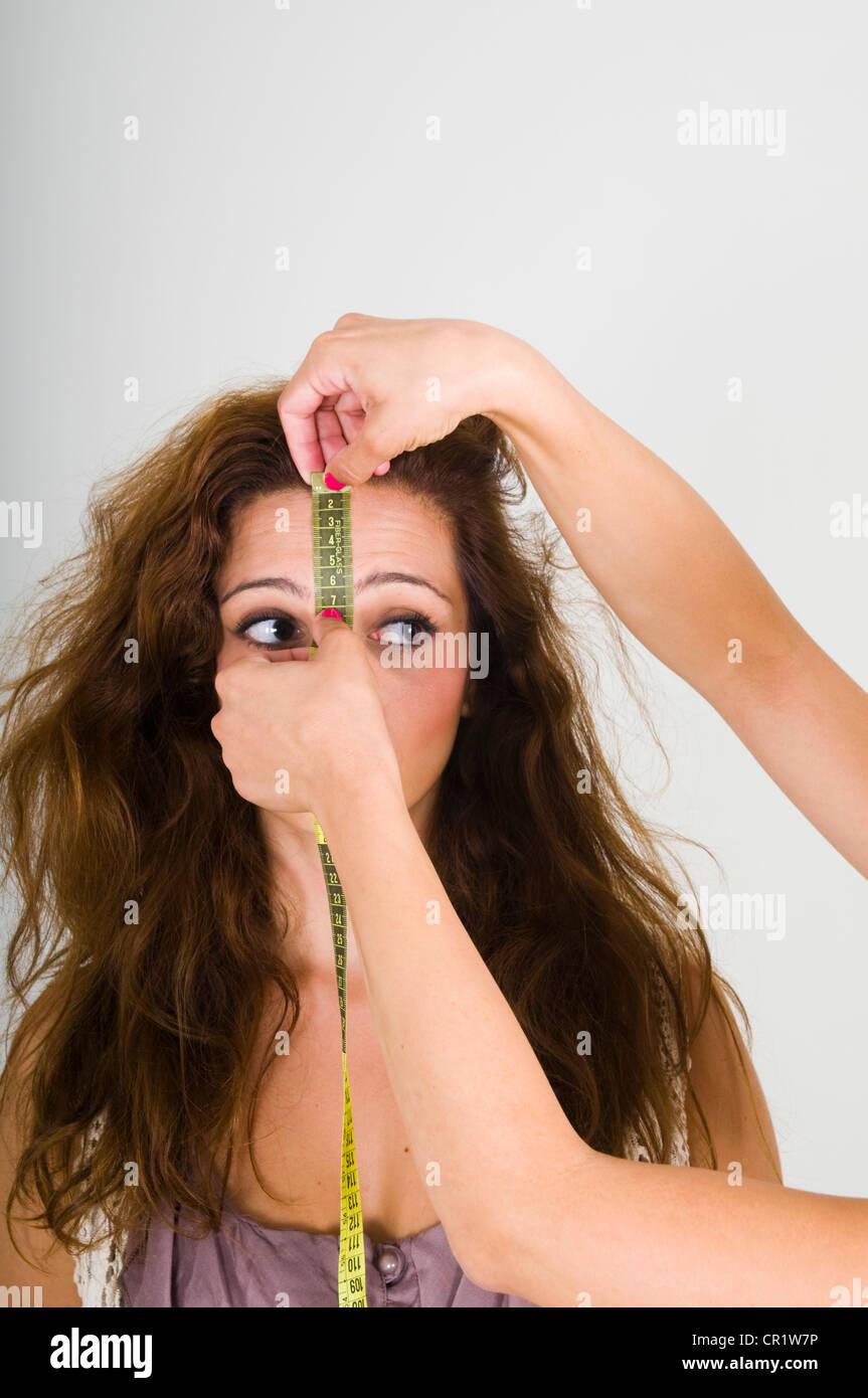 Frau, die Stirn gemessen Stockbild