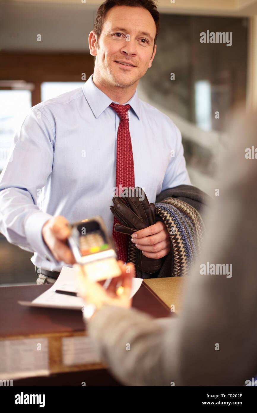 Geschäftsmann zahlt an Rezeption Stockbild