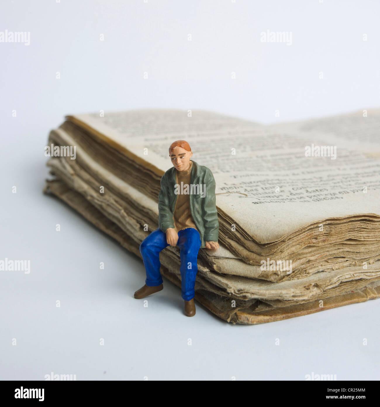 Junger Mann / Student Miniatur Figur, sitzt auf einem alten Buch - Universität / Ausbildung / Studium / Lernkonzept. Stockbild