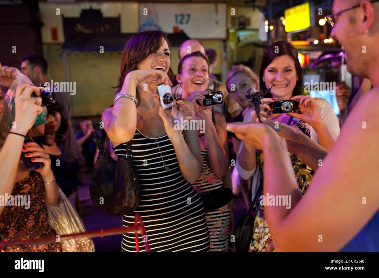 Touristen nehmen ein Foto von einem anderen Touristen Essen einen Skorpion auf der Khao San Road, Bangkok, Thailand. Stockbild