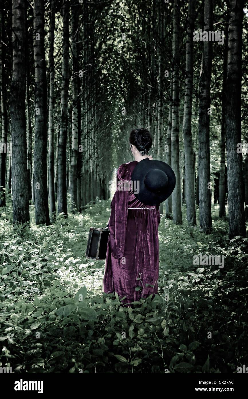 eine Frau geht durch einen Wald mit einem Hut und einem Koffer in einem Zeitraum Kleid Stockbild