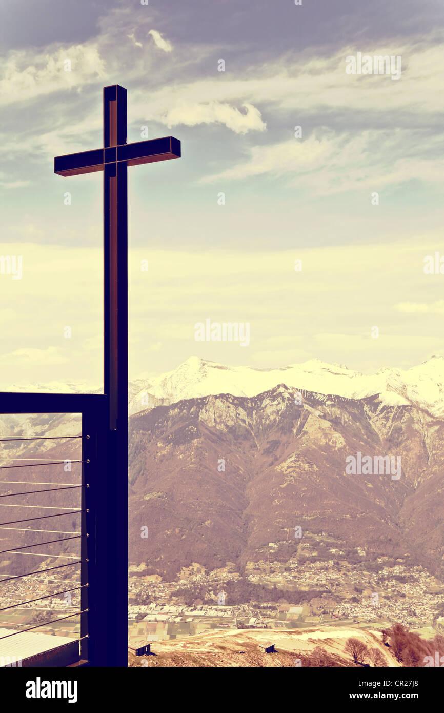 Kreuz auf einem Hügel und die Alpen im Hintergrund Stockbild