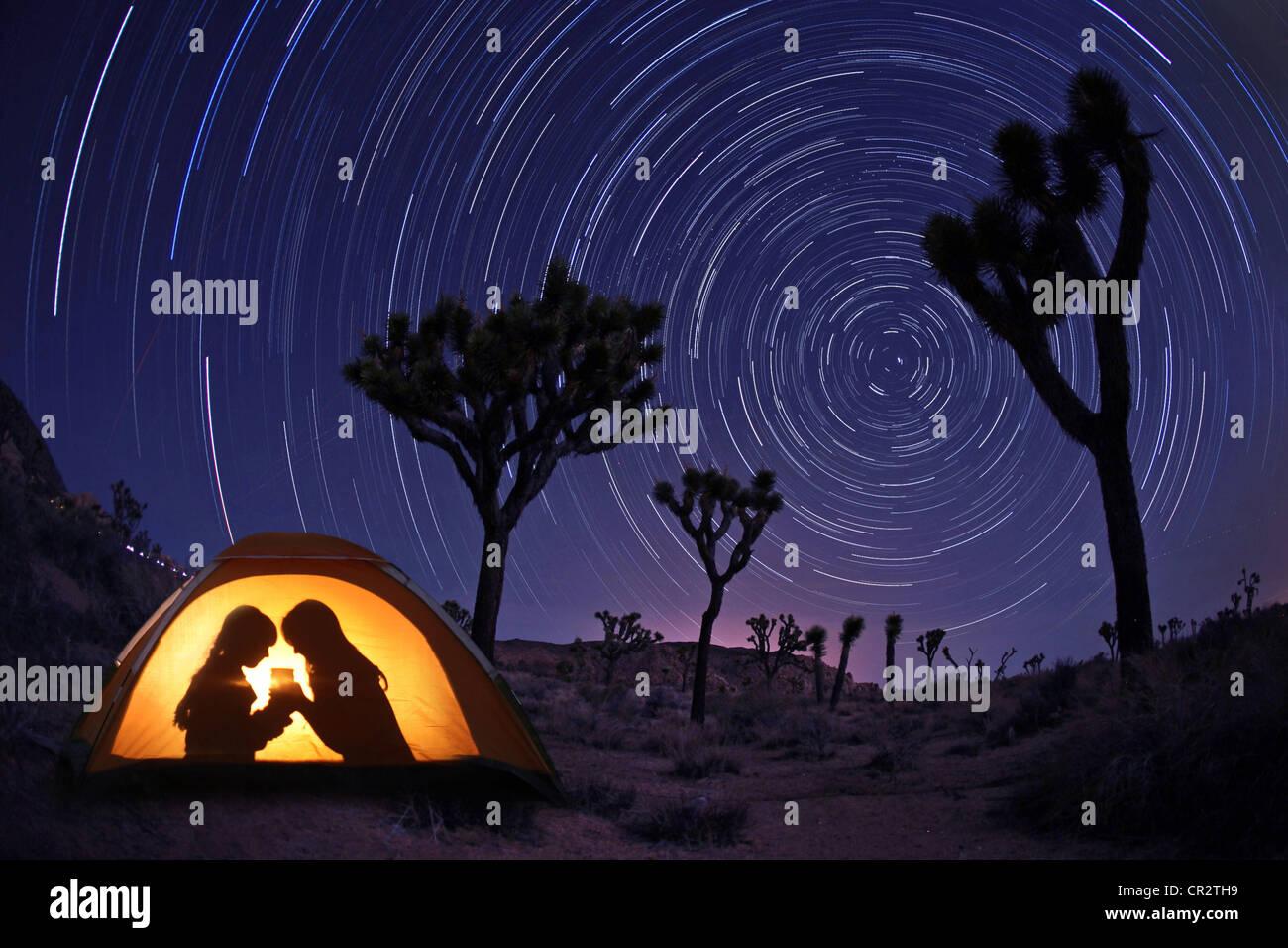 Kinder in der Nacht in einem Zelt mit Sternspuren Camping Stockbild