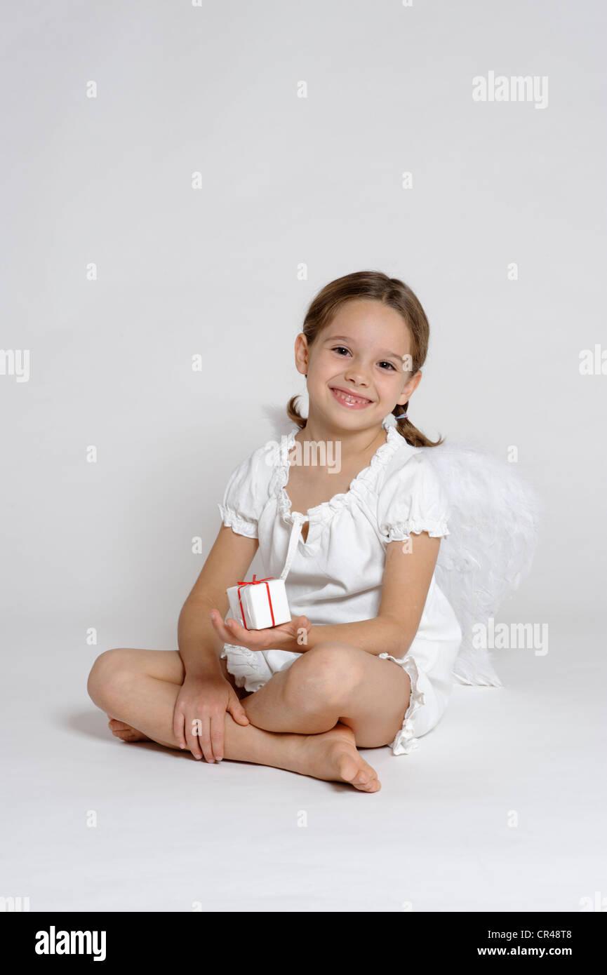 Mädchen, gekleidet wie ein Weihnachtsengel mit einem Geschenk, Weihnachten Stockbild