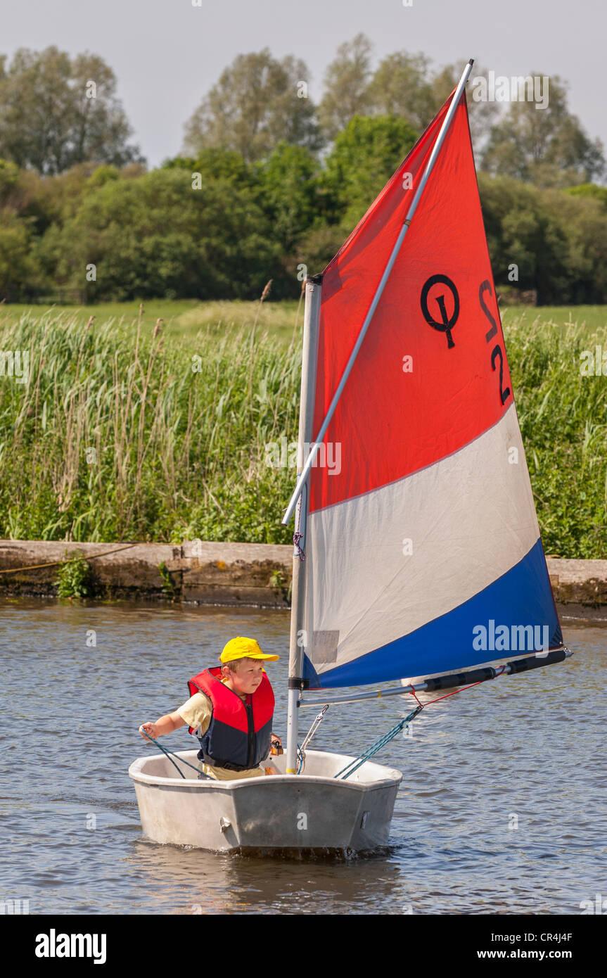 Ein acht Jahre alter Junge Segeln in ein Optimist-Jolle im Vereinigten Königreich Stockbild