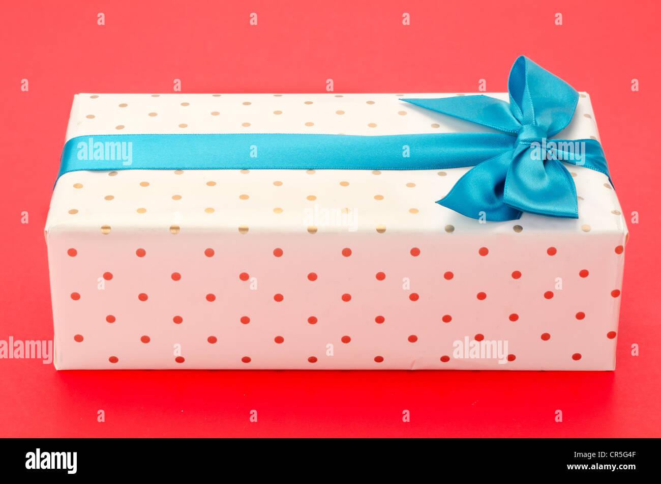 Verpackte Geschenkbox mit einem blauen Band und Bogen - gedreht im Studio mit einem roten Hintergrund Stockbild
