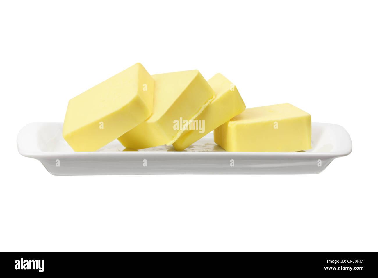 Scheiben von Butter auf Platte Stockfoto