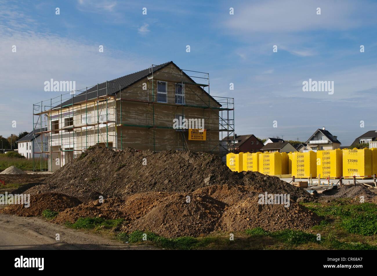 Baustelle, Styropor Dämmung gelagert neben einem Rohbau, umgeben von Gerüsten Stockbild