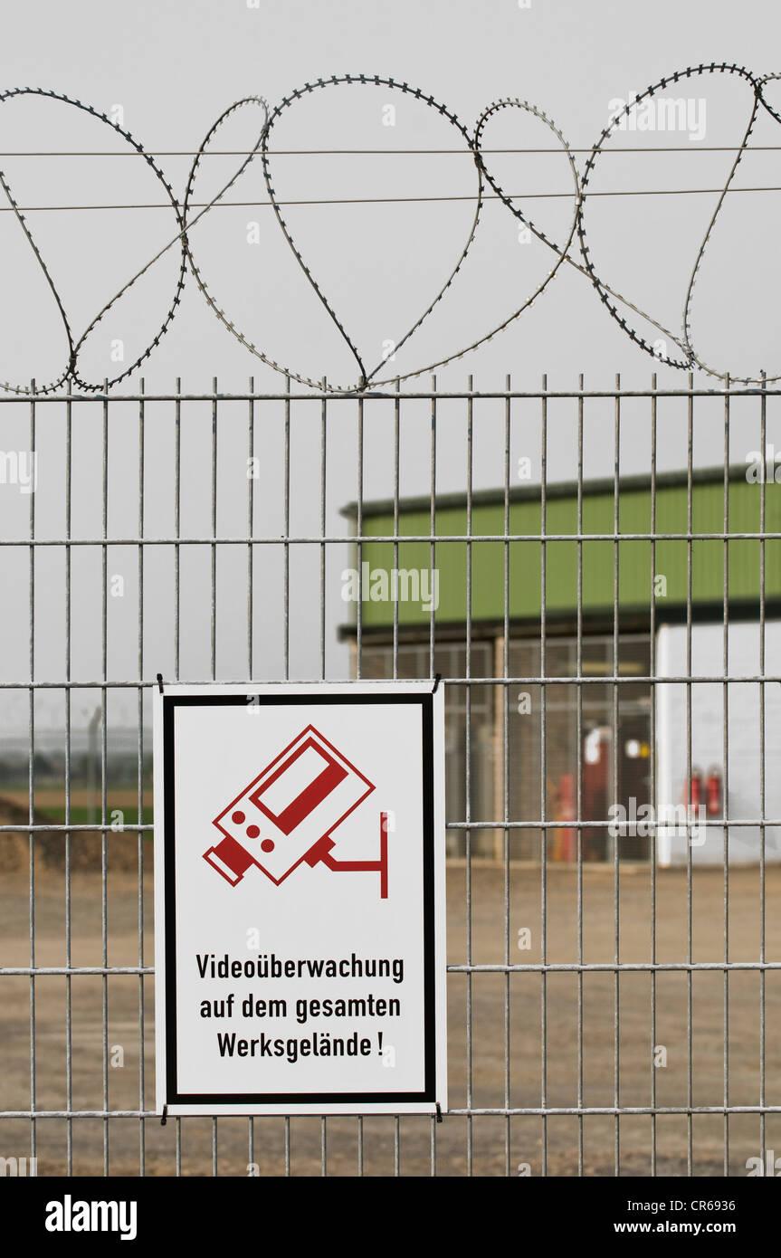 Melden Sie auf einem Zaun mit Stacheldraht, Videoueberwachung Auf Dem Gesamten Werksgelaende, Deutsch für Videoüberwachung Stockbild