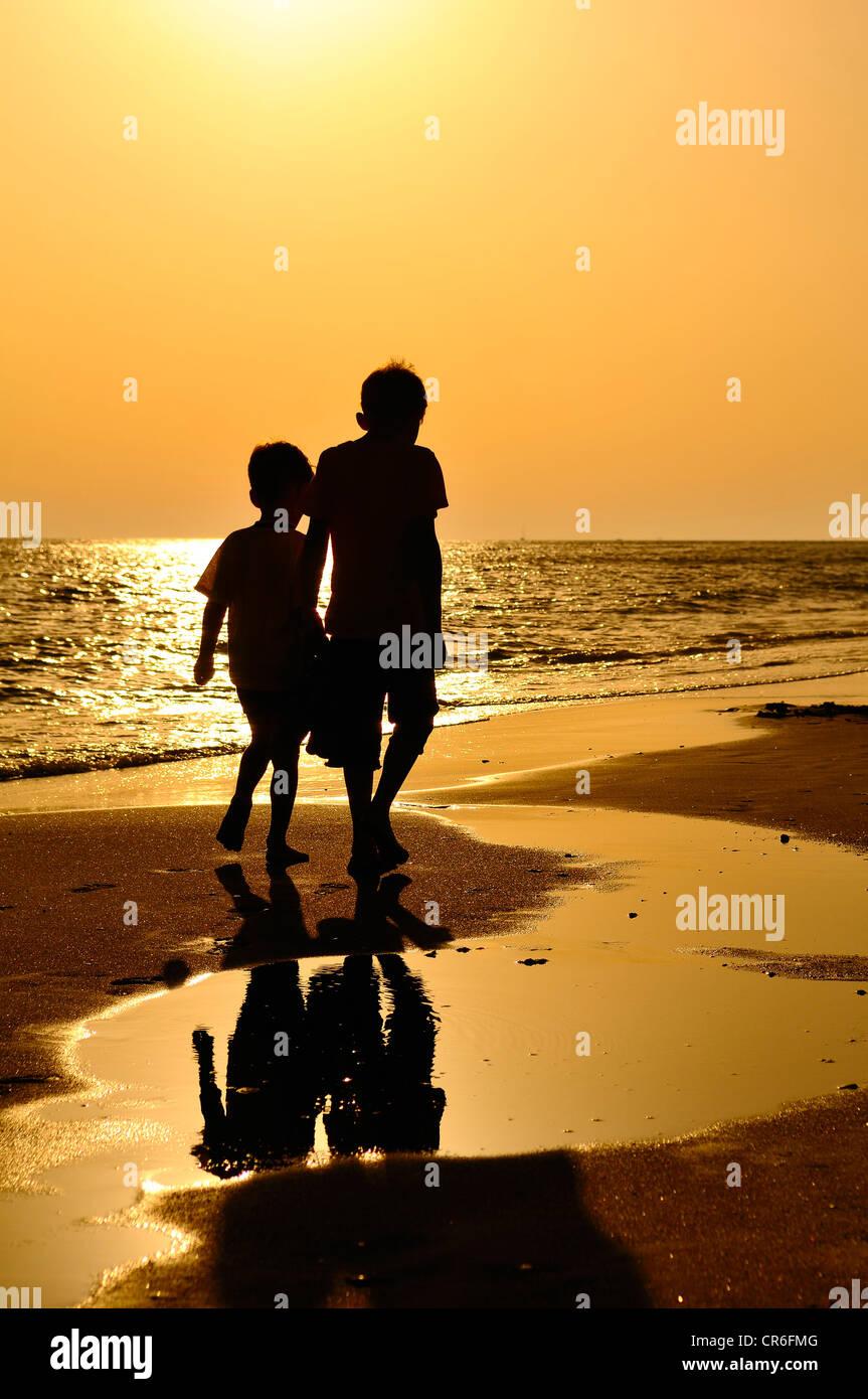 Zwei jungen, die zu Fuß am Strand, Abendstimmung, Lido di Ostia, Rom, Latium, Italien, Europa Stockfoto
