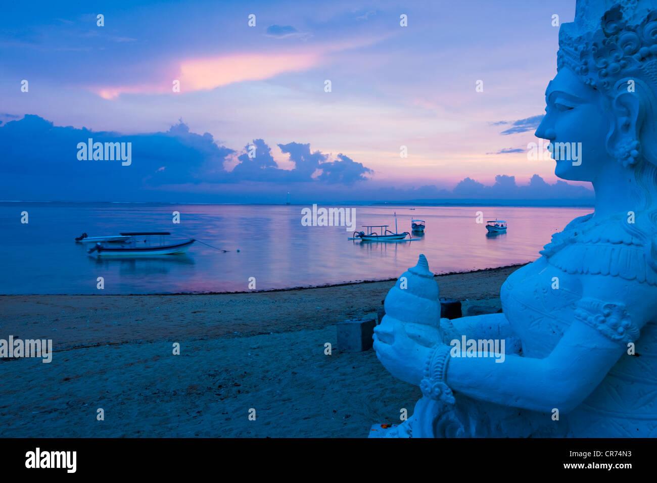 Indonesien, Bali, Sanur, Statue mit Meer im Hintergrund in der Abenddämmerung Stockfoto