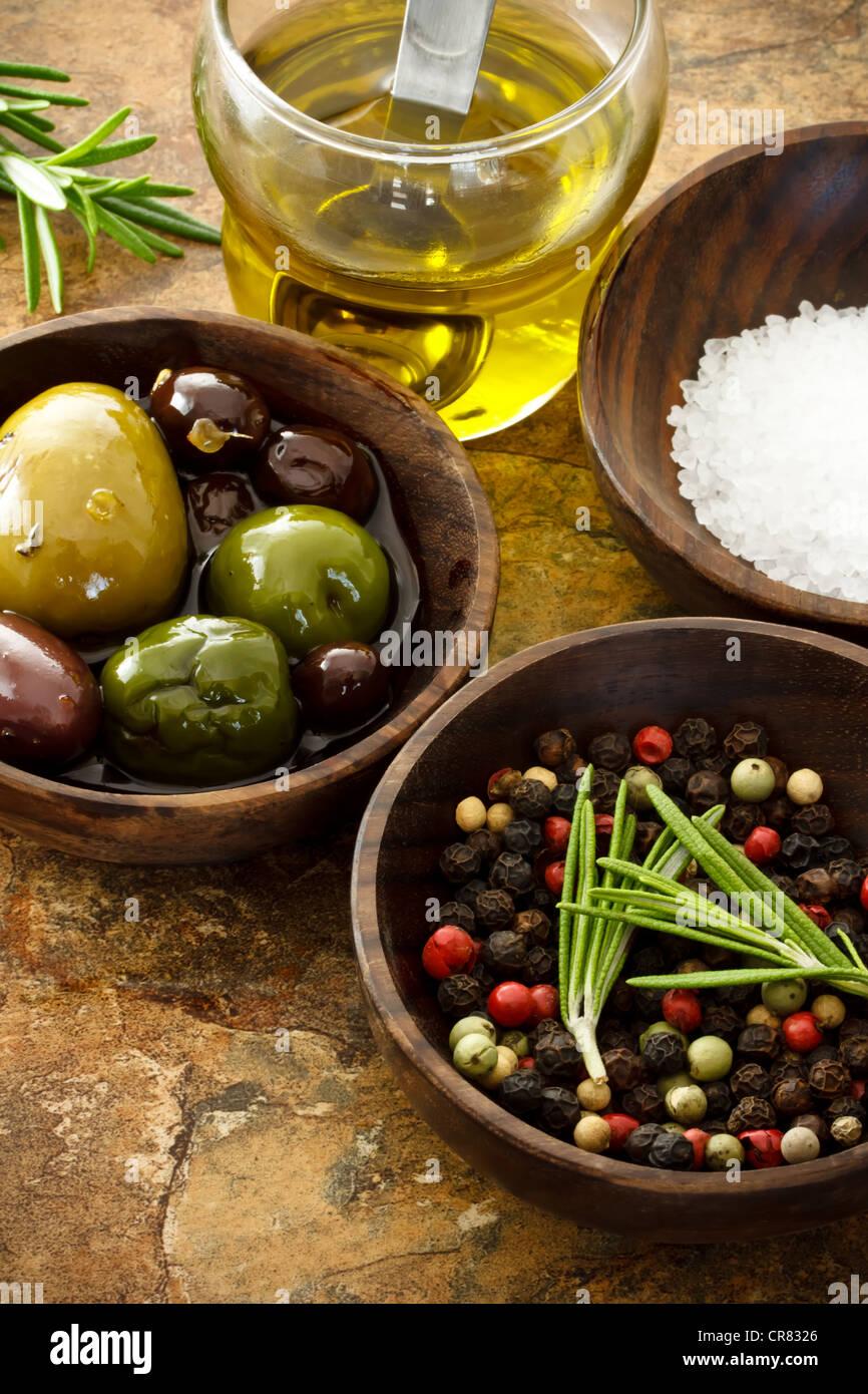 Olivenöl, Pfeffer, Meersalz am Steintisch Stockbild