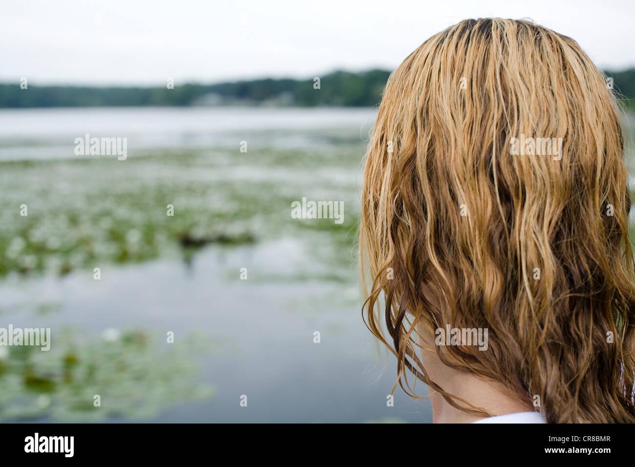 Frau am Rande des Sees mit nassen Haaren Stockbild