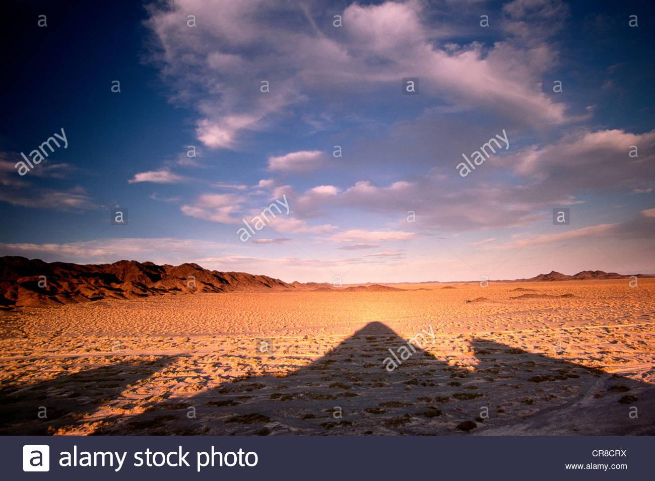 Die Sonne geht hinter den Bergen, die wiederum ihre langen auf das Tal Schatten, Mongolei. Stockbild