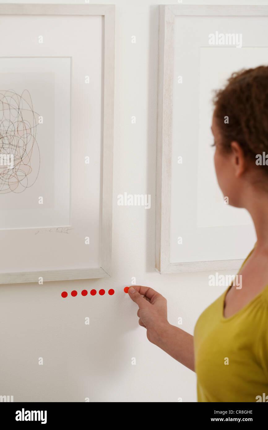 Kunsthändler Platzierung verkauft Punkte unter Kunstwerke in der Galerie Stockbild