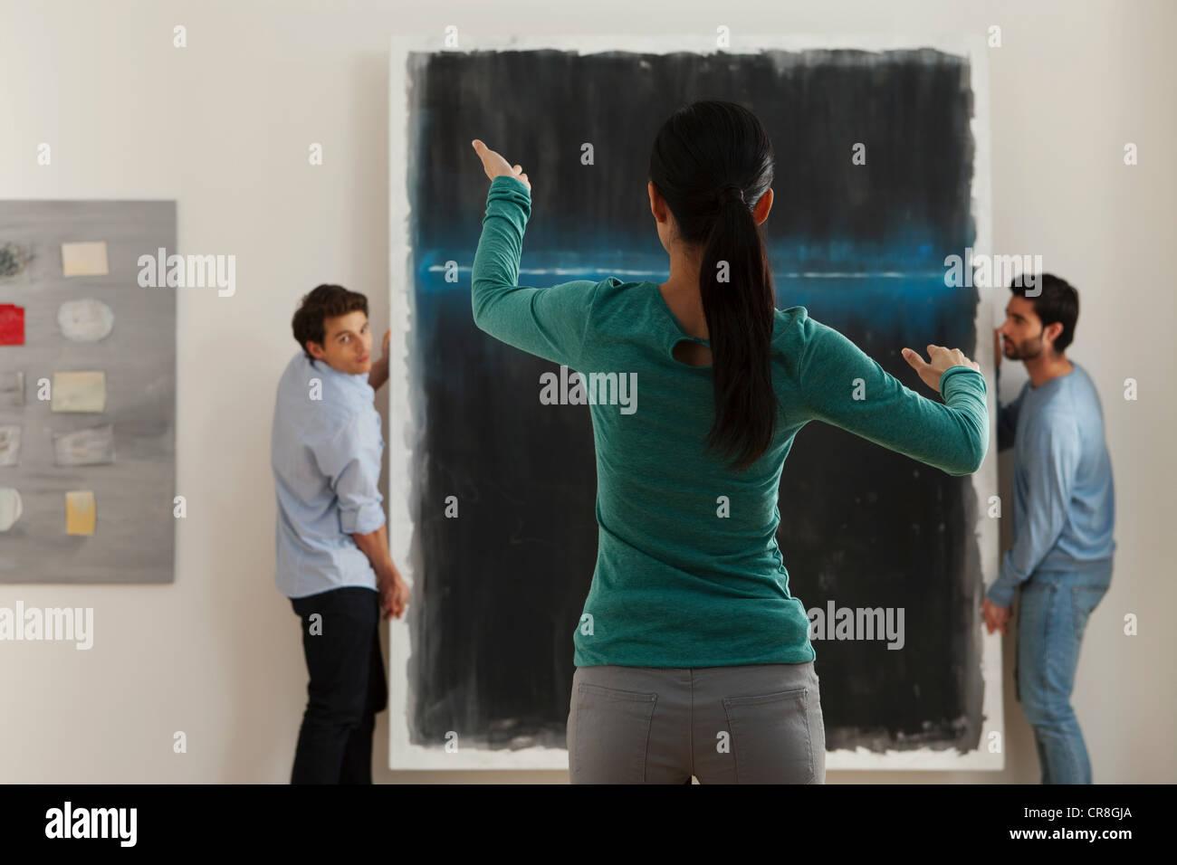 Kunsthändler, die Vermittlung von hà ¤ ngen des Öl-Malerei in der Galerie Stockbild