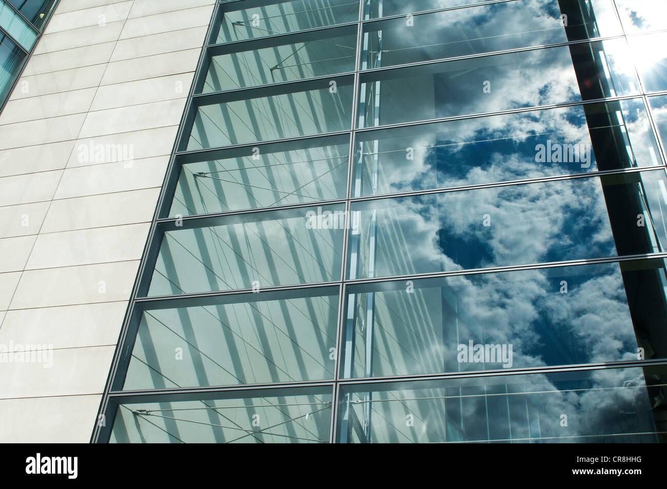Bewölkten blauen Himmel spiegelt sich in Bürofenster Stockbild