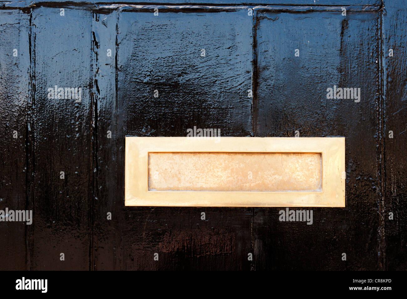 Ein gold Metall Briefkasten auf einem schwarz lackierten Tür. Stockbild
