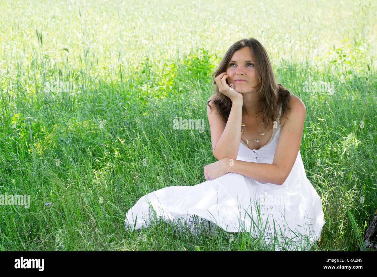 Eine Frau sitzt auf einer Wiese lächelt sich während Tagträumen Stockbild