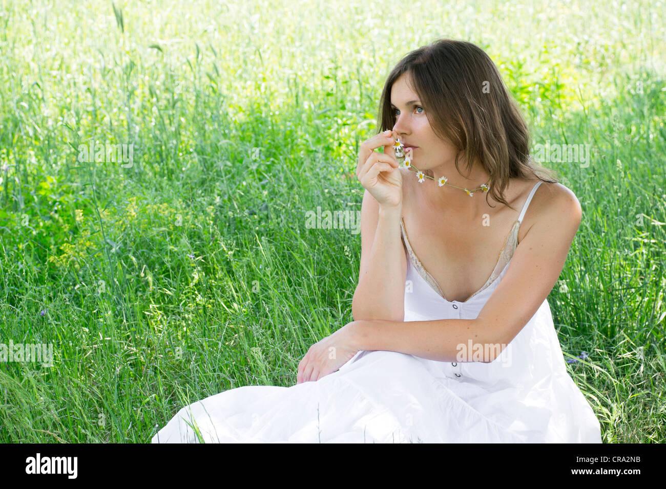 Schöne junge Frau hält einen Daisy-Chain, sitzen auf einer Wiese Stockbild