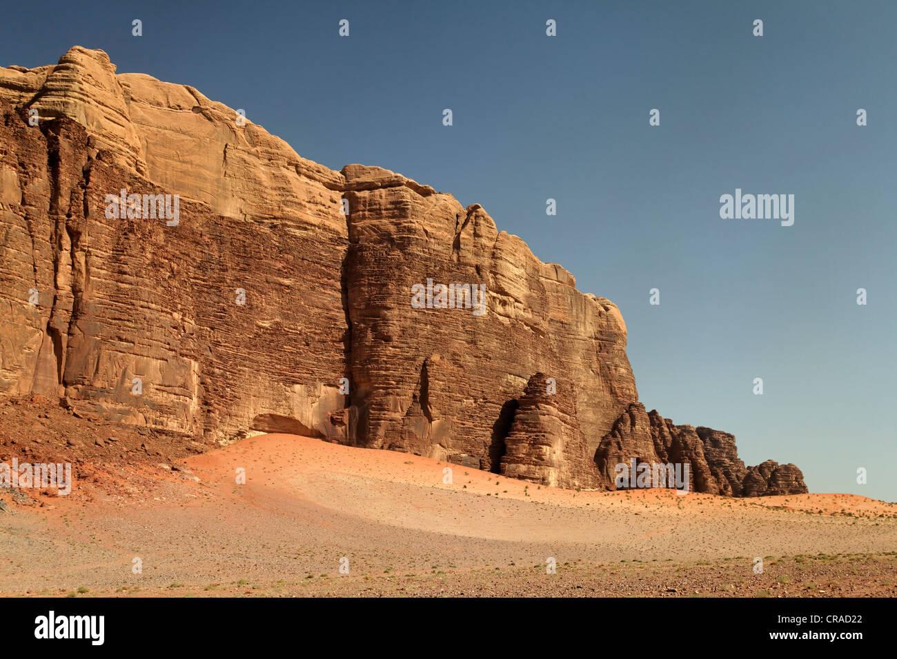 Wüste Ebene mit einem steigenden Bergmassiv, Wadi Rum, Haschemitischen Königreich Jordanien, Naher Osten, Stockbild
