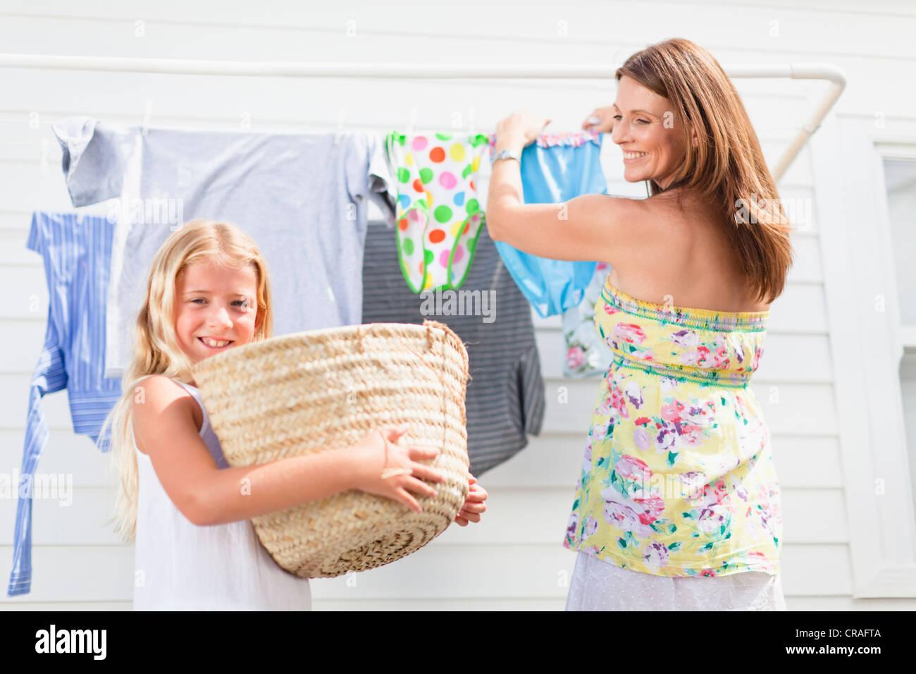 Mädchen helfen Mutter hängen Wäsche Stockbild