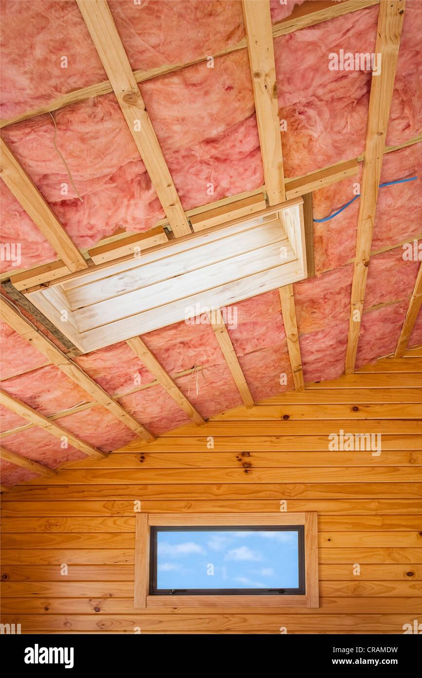 Fiberglas Isolierung in der Dachschräge eines Holzhauses installiert. Stockfoto