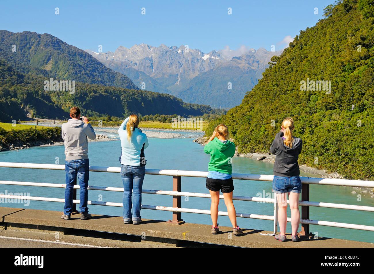 Touristen fotografieren des Whataroa-Flusses, mit Blick auf die südlichen Alpen, Westküste der Südinsel Stockbild