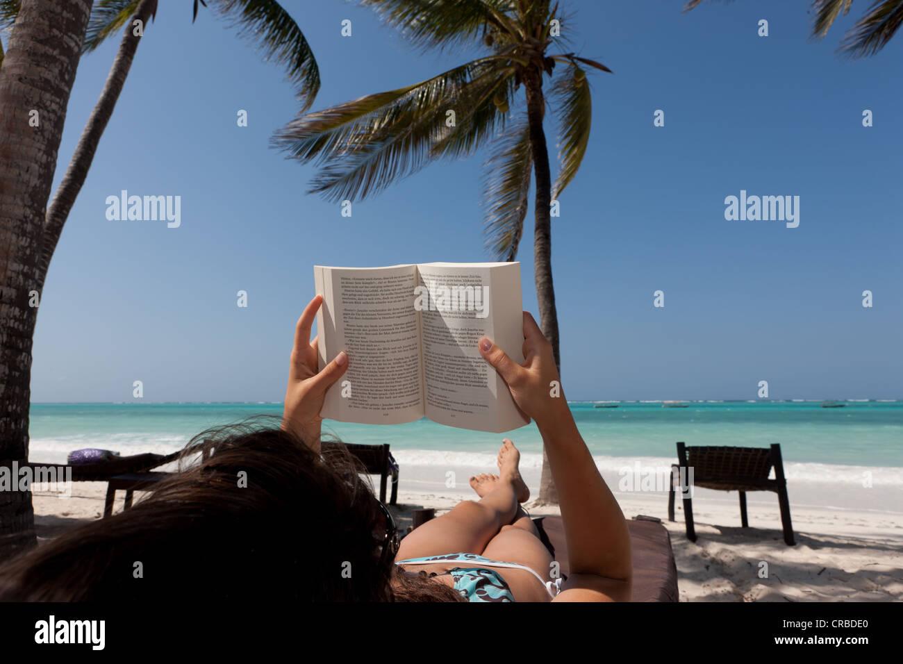 Mädchen, 16 Jahre, lesen ein Buch am Strand unter Palmen Stockbild