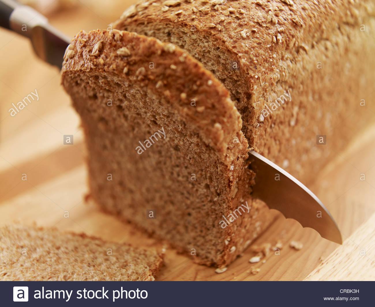 Messer schneiden frischer Brotlaib Stockbild
