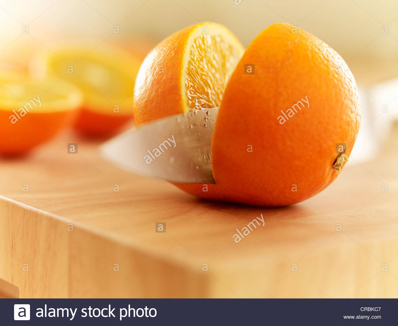 Messer schneiden Orange auf Schneidebrett Stockbild