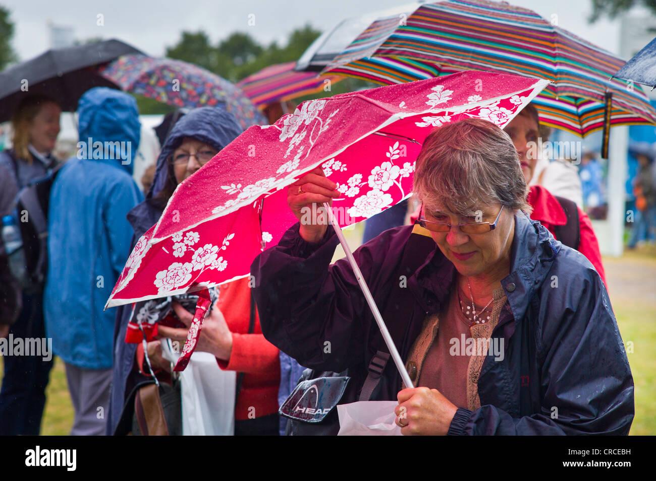 Viele Menschen mit Regenschirmen im RHS Hampton Court Flower show 2011 Stockbild