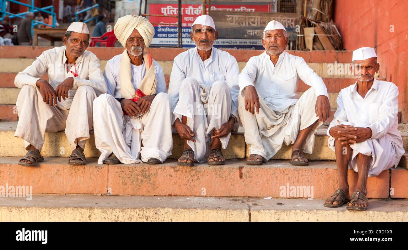 Hindu-Pilger sitzen auf den Ghat von Varanasi, Uttar Pradesh, Indien Stockbild