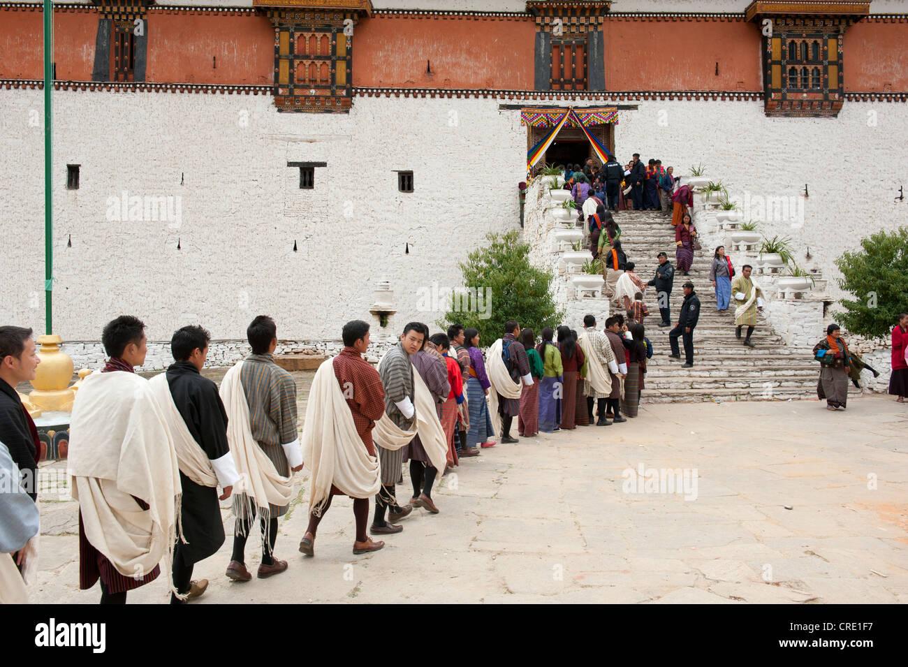 Tibetisch-buddhistische Festival Gewand Menschen tragen die traditionelle Gho stehen in einer Warteschlange, Rinpung Stockbild