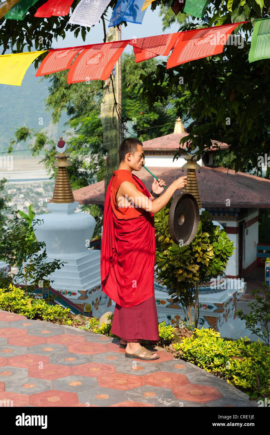 Tibetischen Buddhismus, Mönch in ein rotes Gewand den Gong zu schlagen, Kharbadi Gompa, Phuentsholing, Königreich Stockbild