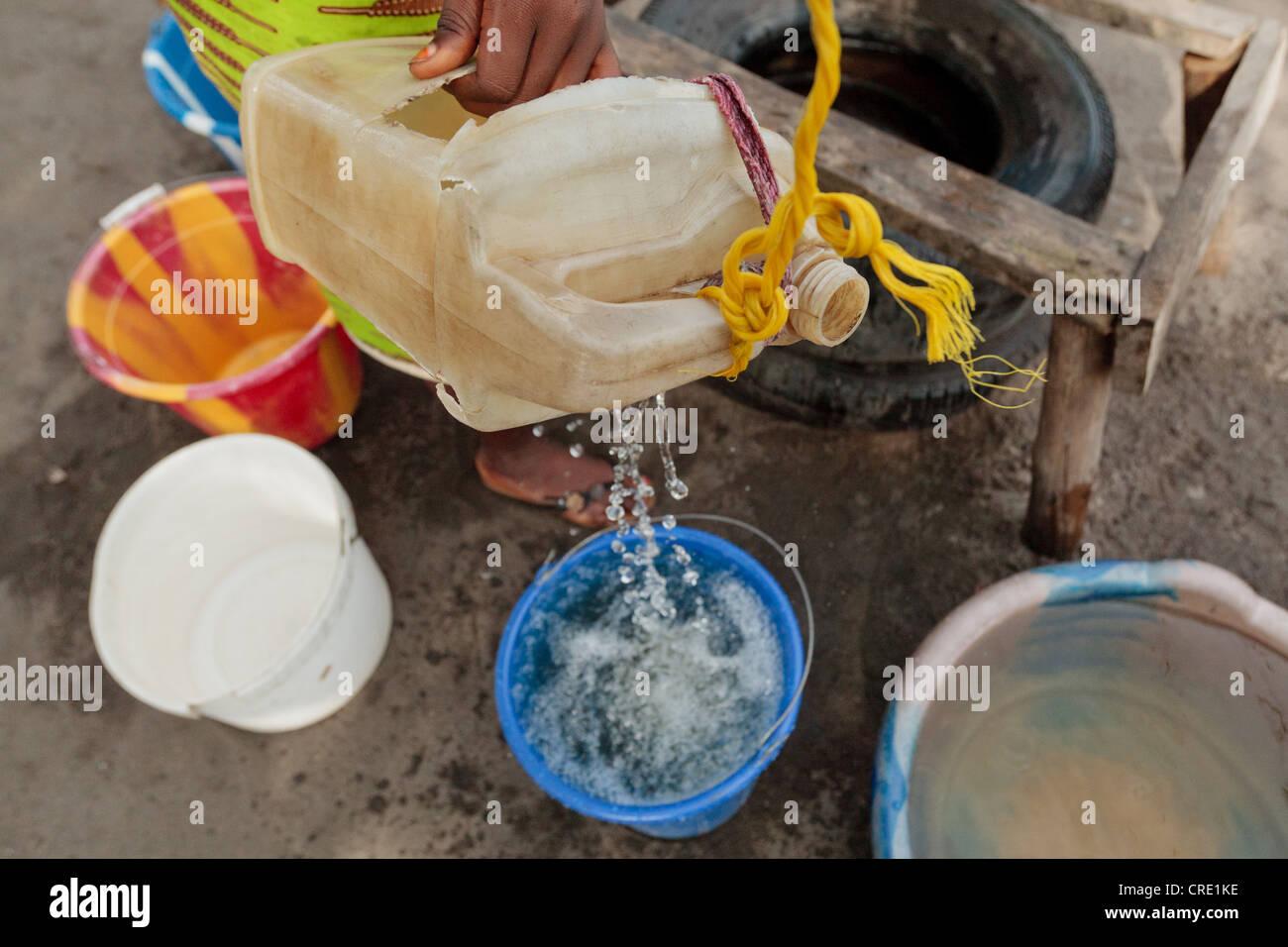 Ein junges Mädchen zieht das Wasser aus einem Brunnen im Stadtteil Punkt vier von Monrovia, Liberia Stockbild
