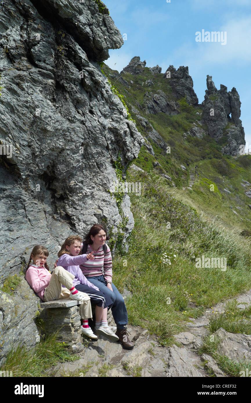 Mutter und zwei Kinder sitzen auf einer Bank in der Nähe von Salcombe Hafen am Schraubenkopf an der südlichen Stockbild