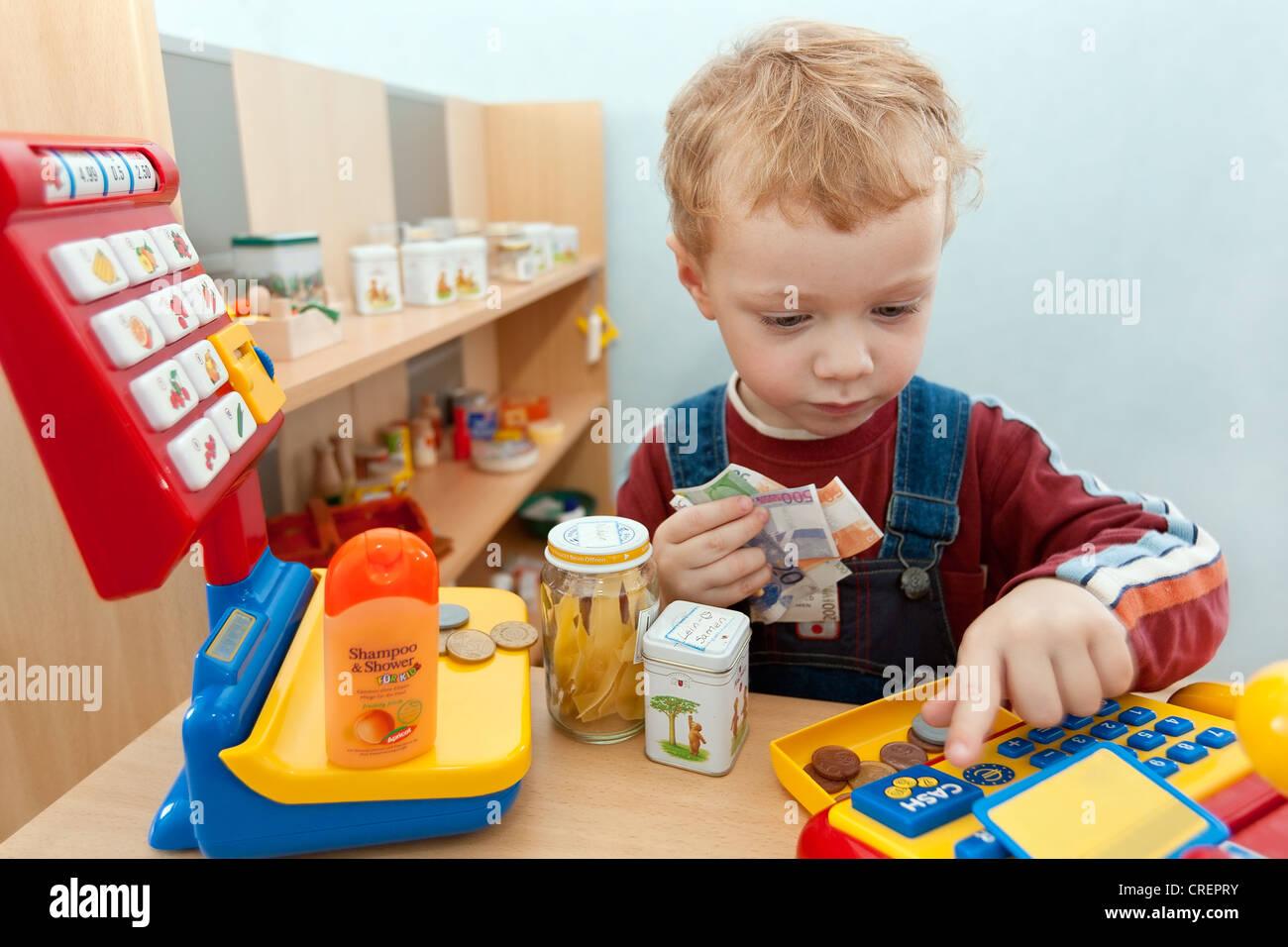 Junge, 2, spielen mit einem Spielzeug-Lebensmittelgeschäft Stockbild