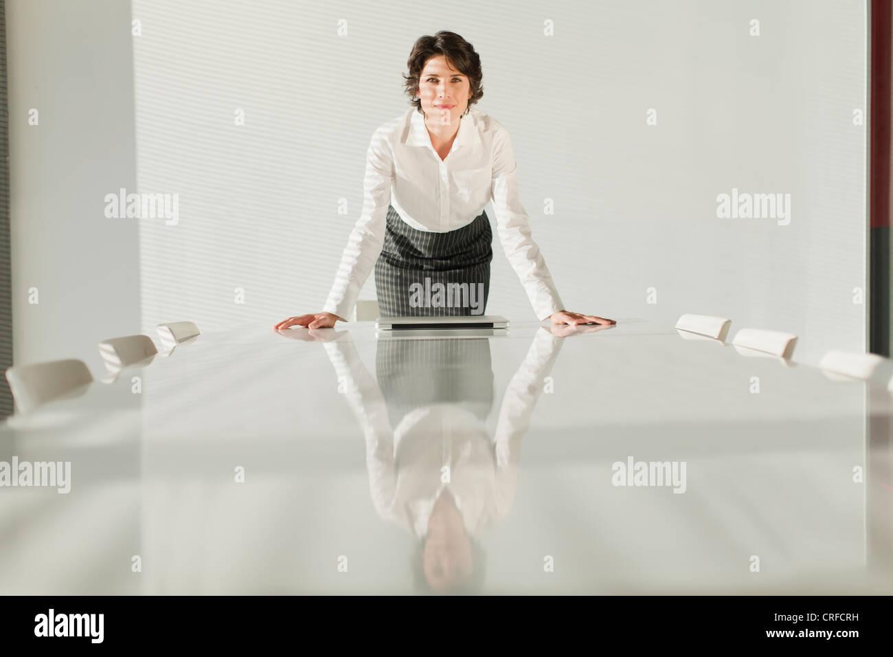 Geschäftsfrau, die in Tabelle übernommen Stockbild