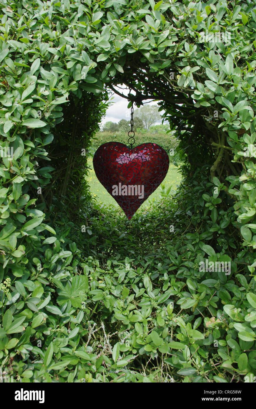 Herzförmige Garten Glasbaumbehang positioniert in einem Spalt in