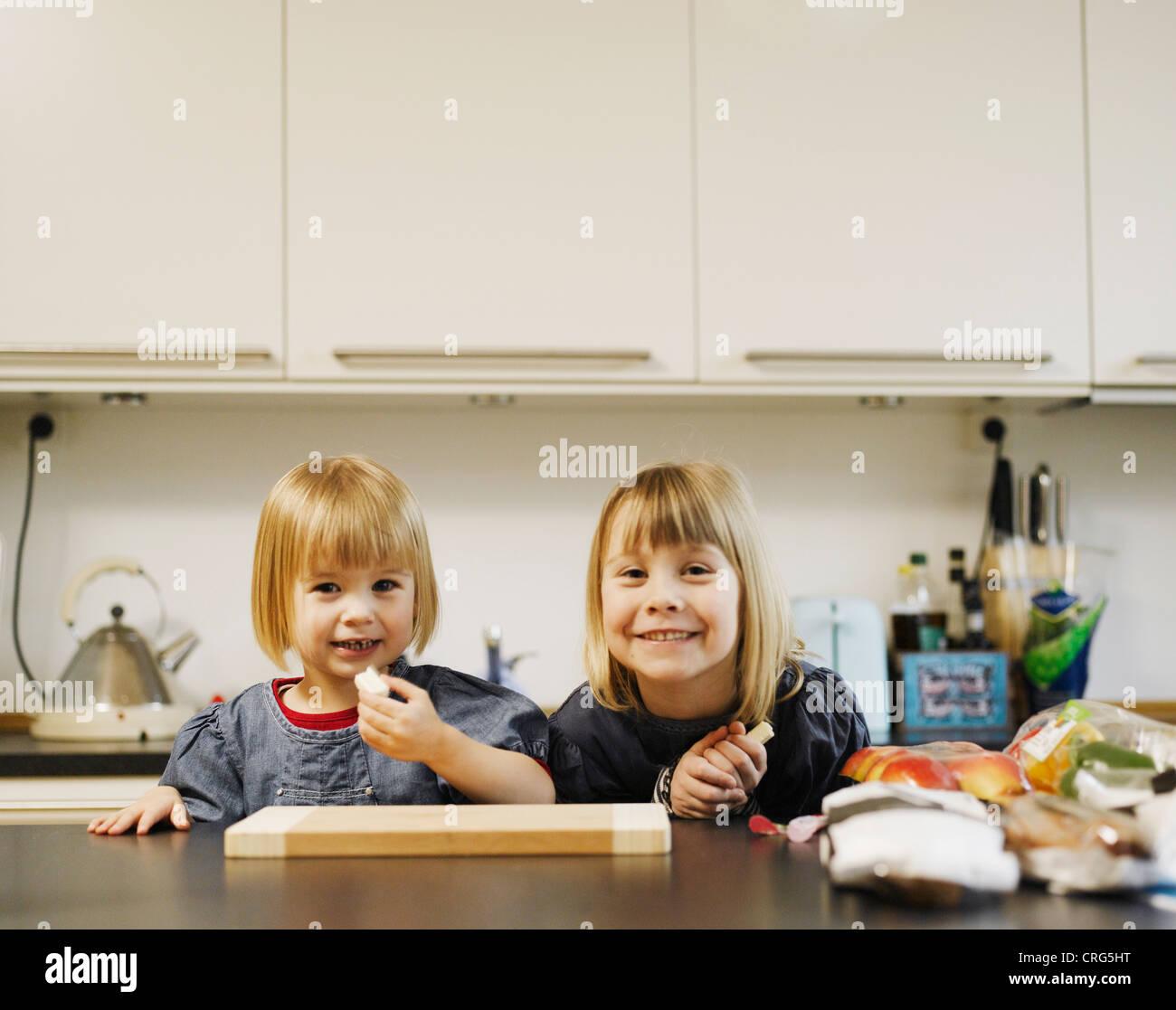 Lächelnde Mädchen Essen in der Küche Stockbild