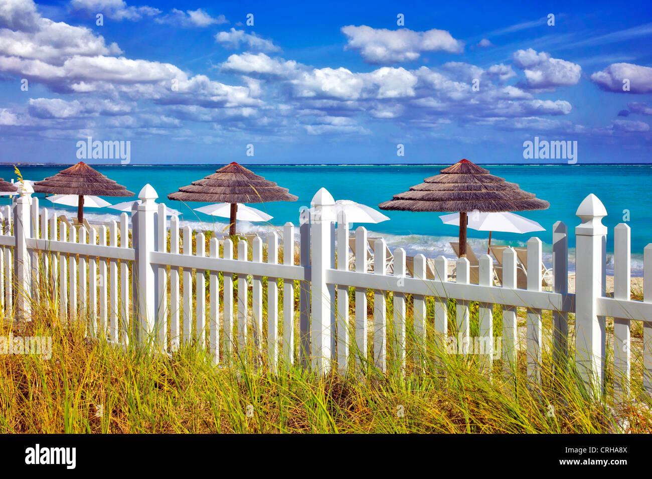 Weißen Lattenzaun und Sonnenschirmen. Grace Bay. Providenciales. Turks- und Caicosinseln Stockbild