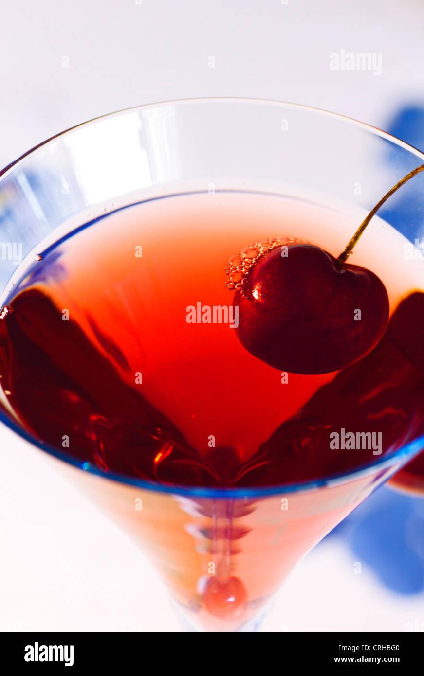 Nahaufnahme von Baccarat blaue Glas mit Saft aus roten Früchten und Red Cherry auf der Felge Stockbild