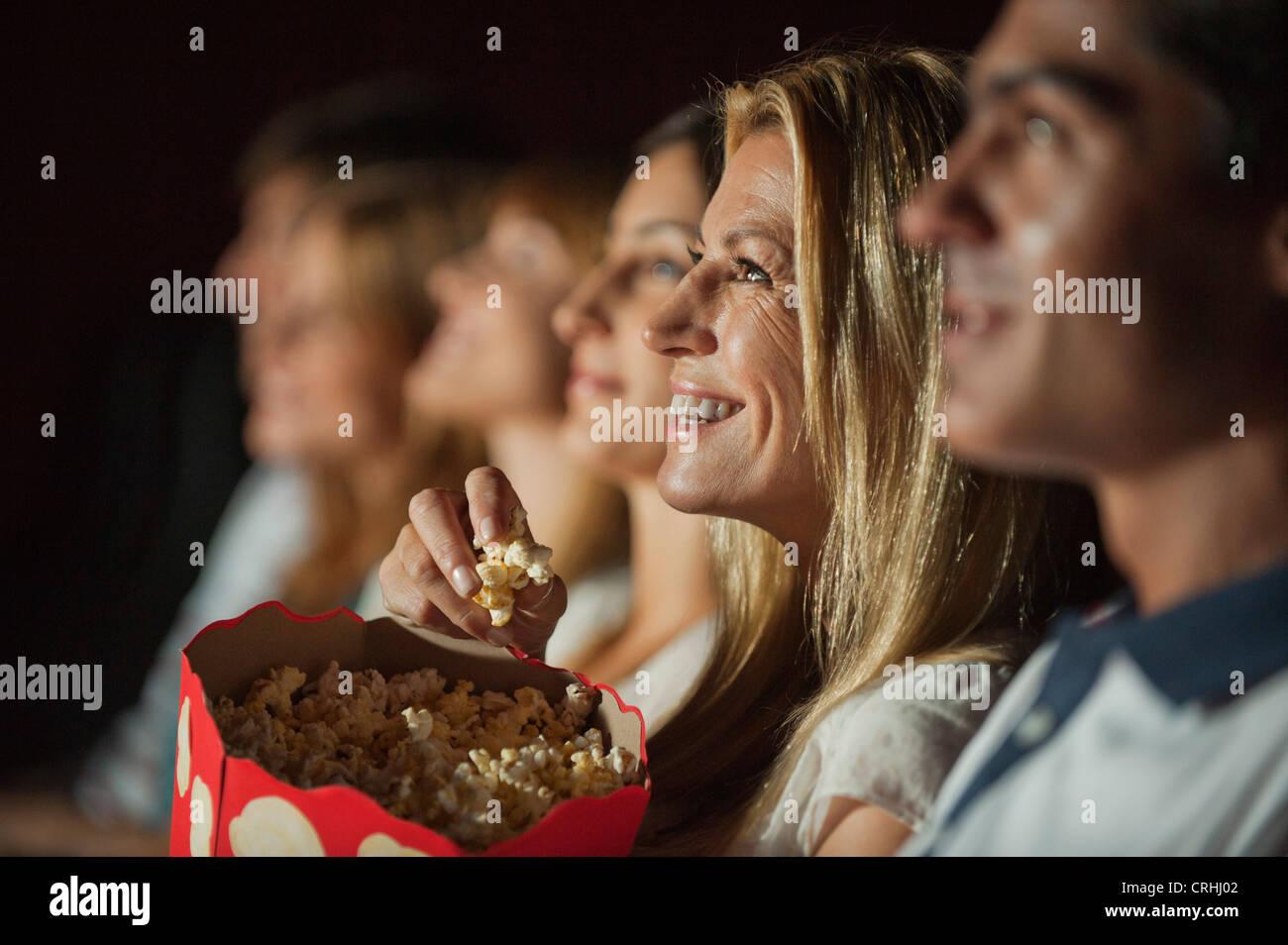 Frau Essen Popcorn bei Film im theater Stockbild