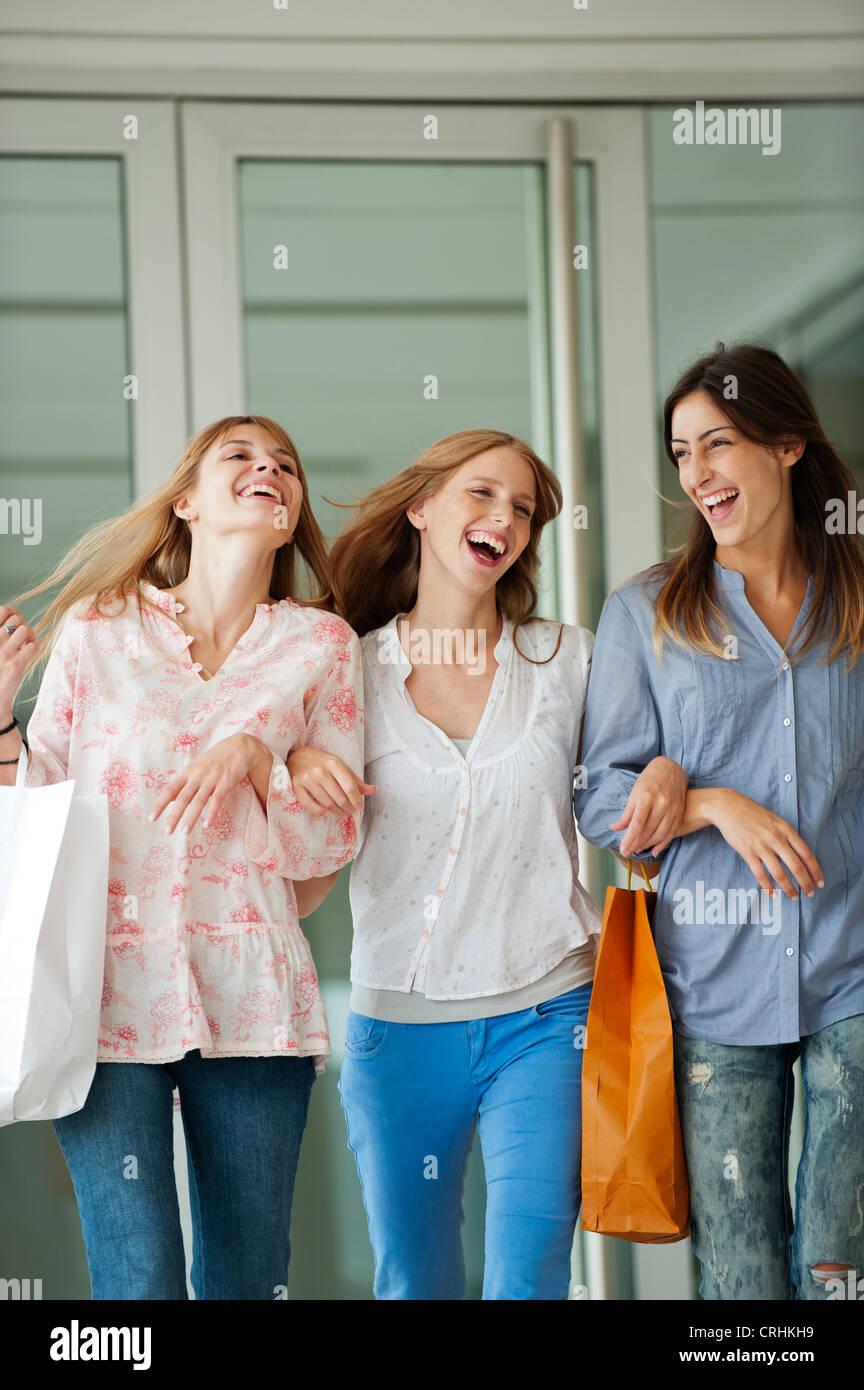 Junge Frauen zusammen spazieren, Einkaufstaschen tragen Stockbild