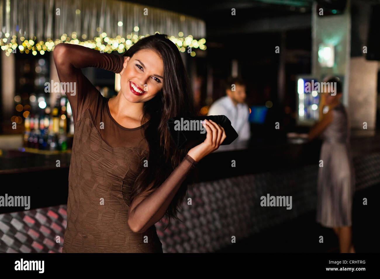 Lächelnde Frau in bar stehend Stockbild