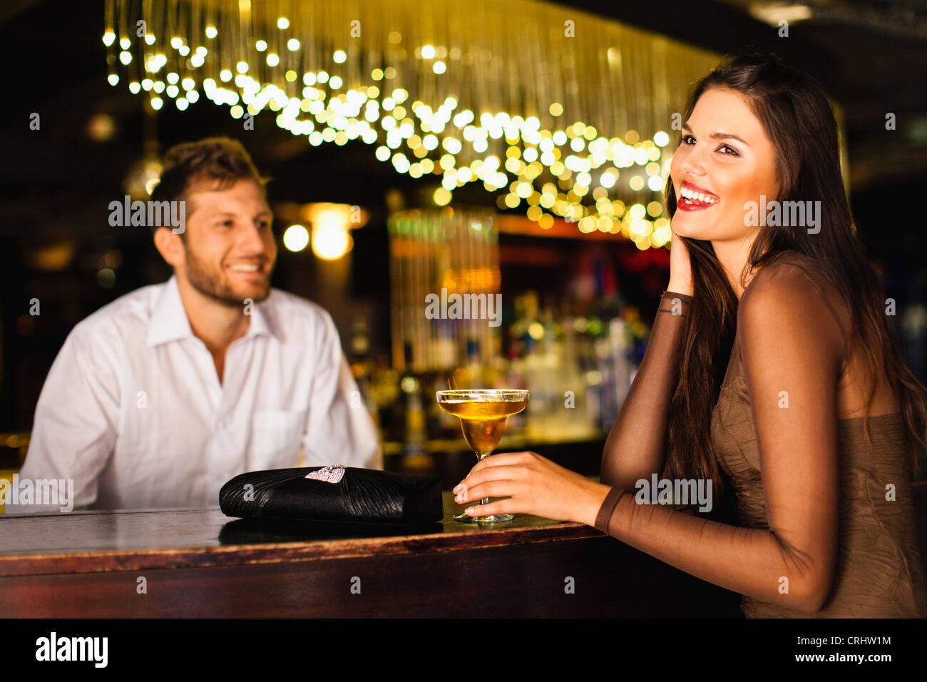 Frau im Gespräch mit Bartender bei Bar Stockbild
