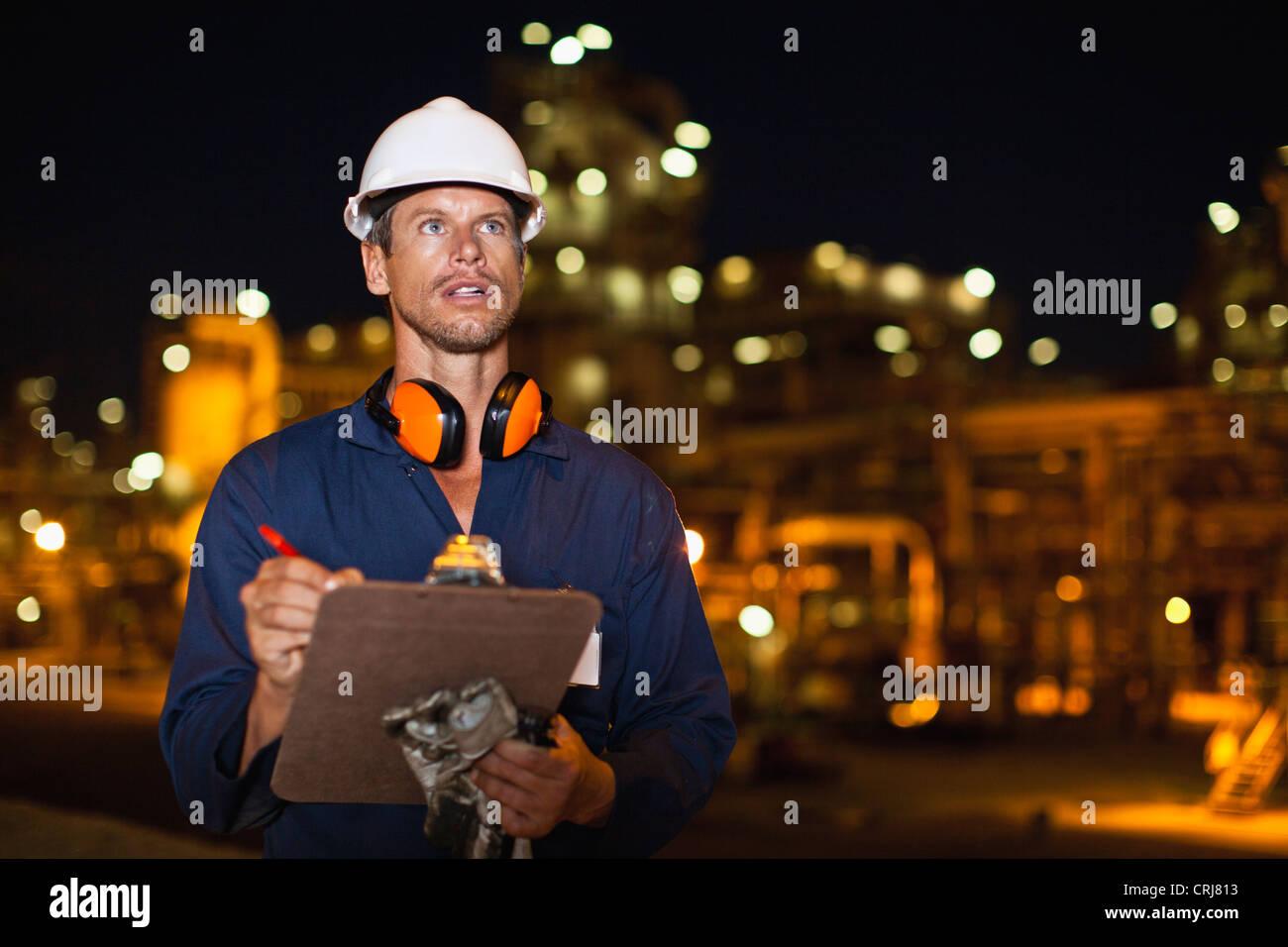 Arbeiter mit Zwischenablage am Öl-Raffinerie Stockbild