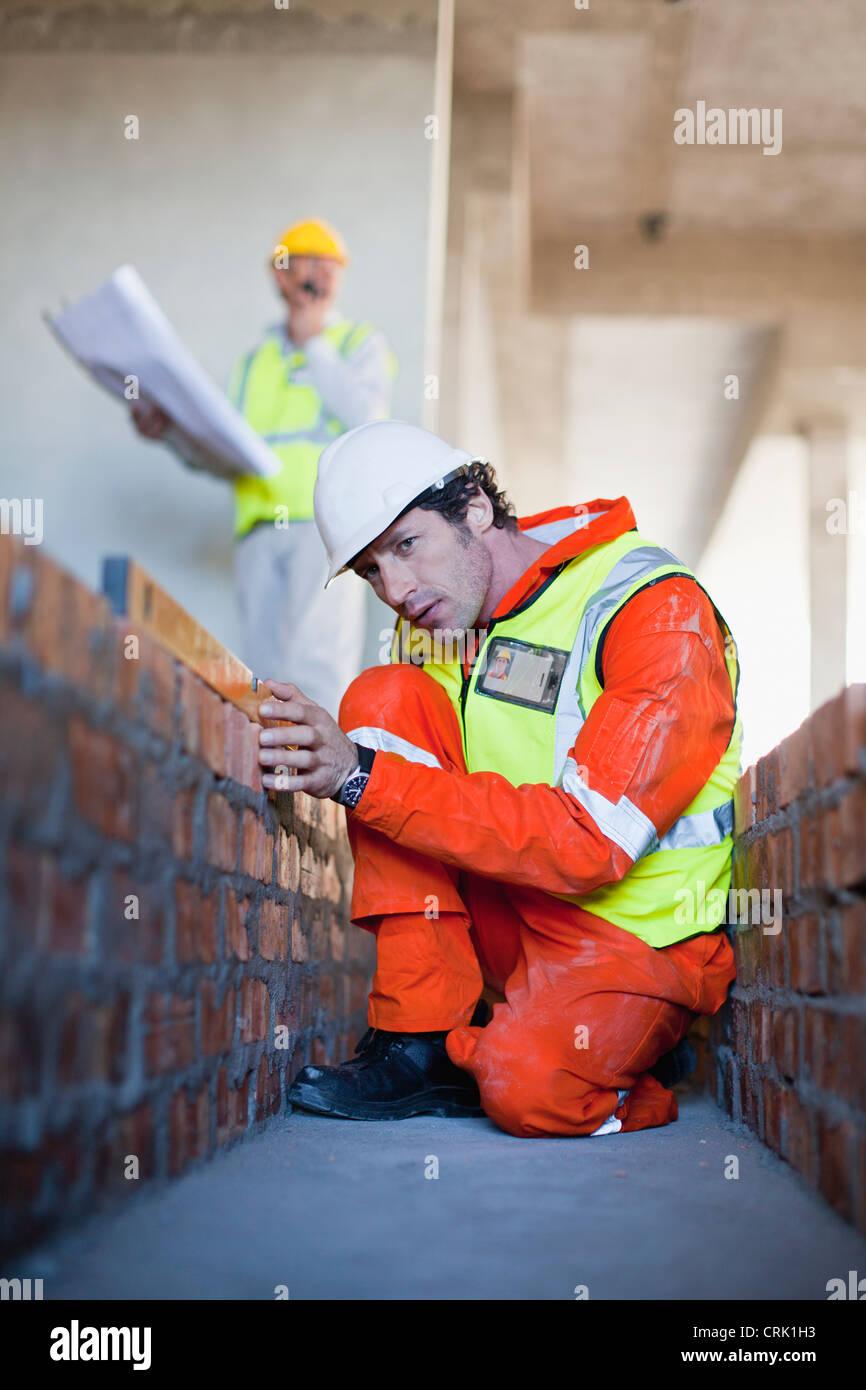 Arbeiter verlegen Ziegel auf Baustelle Stockbild
